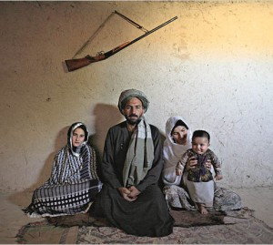 Portrait of Mohammed Fazal, 45, with his two wives (L-R) Majabin, 13, and Zalayha, 29 in the village on the outskirts of Mazar Al Sharif. Fazal was offered Majabin as a debt settlement when a fellow farmer could not pay after a night of playing cards. They have been married for six months.