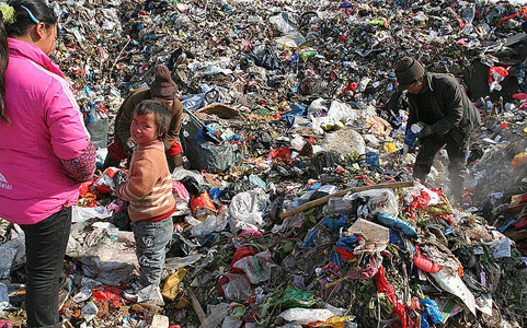 """Garbage Family""  Despite China's rapid economic growth and strict no-migration laws, there remains a marked disparity between the country's wealthy and the poor. This family, originally from Guizhou Province (far-western China) moved to the rich Delta Yangtze River coast in search of a better life. They currently work in a Jiangsu landfill, sifting through garbage in search of any re-sellable items.  In a country of 1.35 billion people (and still growing!) -- is there any room for Pandas or any other wildlife?  Photo and commentary by Sheilaz314/Flickr/cc"